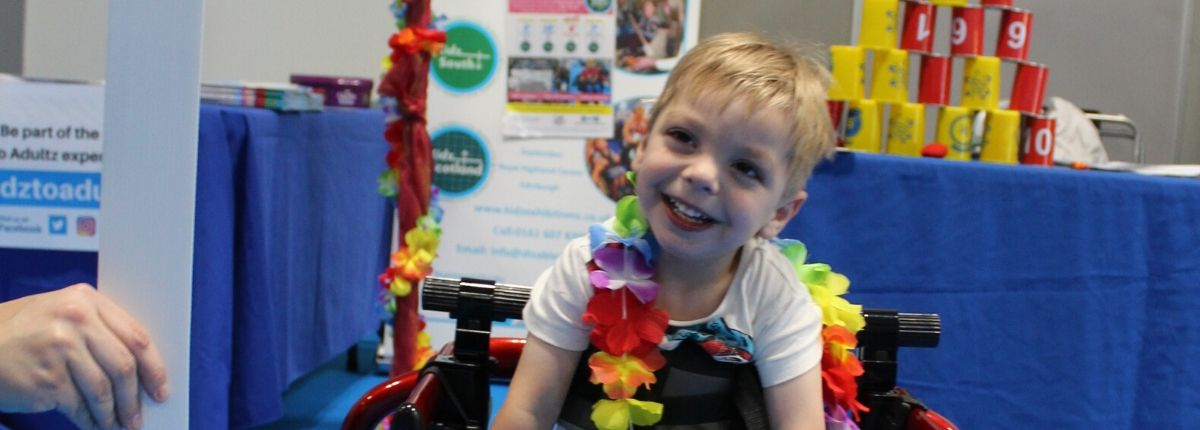 young boy smiling with hawaiian flowers around his neck