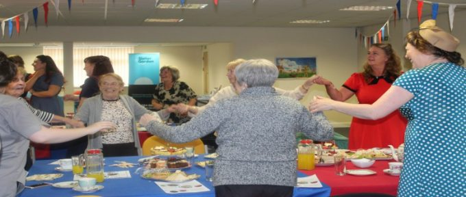 people dancing around the table at disabled living 1940's tea dance