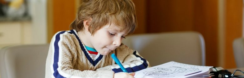 young boy using his colouring in book with his blue pen