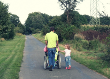 father pushing wheelchair and walking with his daughter down the road