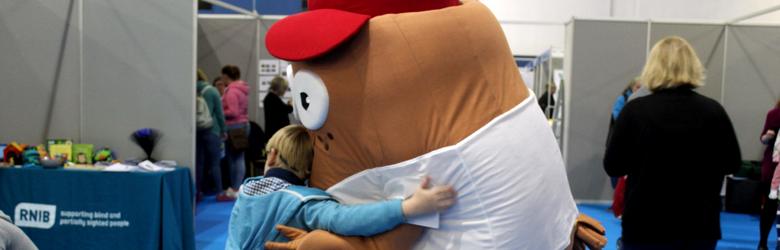 child giving mascot a hug