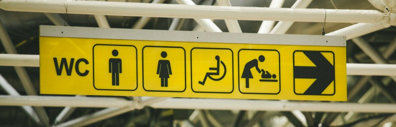 public toilets sign with icons and arrow