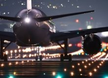 aeroplane landing at airport at night