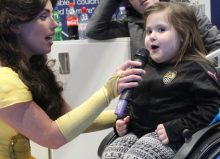 little girl in wheelchair singing through microphone