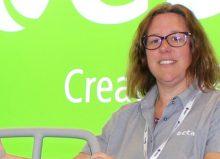 Jo stood at etac exhibition stand holding onto equipment