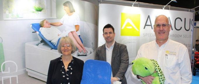 three abacus representatives stood at their exhibition stand