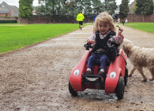 young girl riding a wizzybug with dog in the background