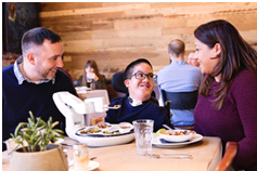 young person in robotic dining companion with people either side smiling