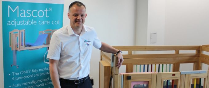 shaun stood by care cot at Theraposture stand