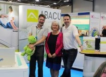 kate with two abacus colleagues stood at their stand