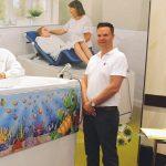 adam stood next to bath on exhibition stand